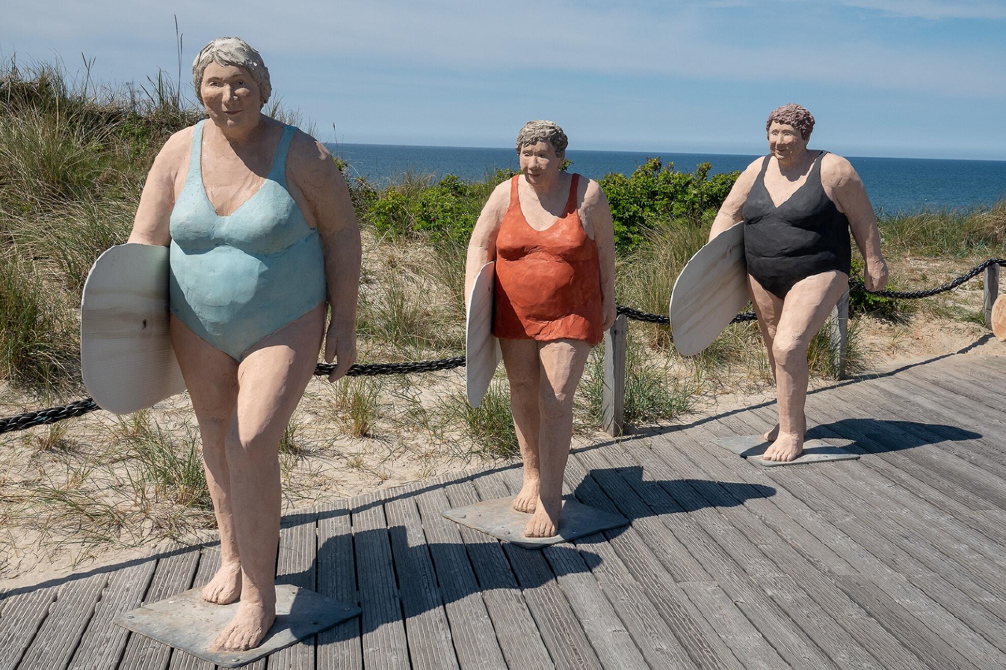 Drei Surferinnen auf der Promenade