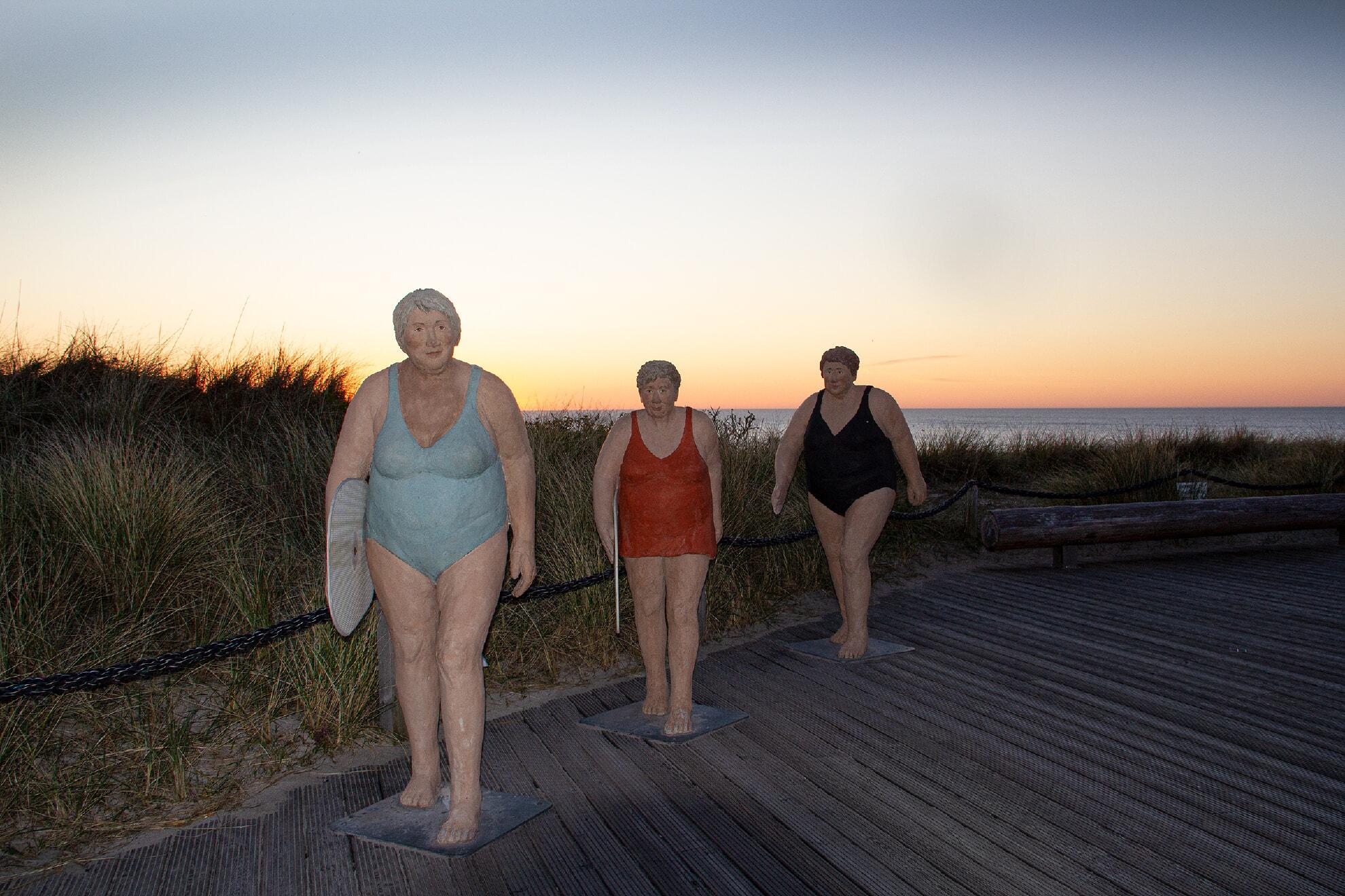 Drei Surferinnen vor Sonnenuntergang